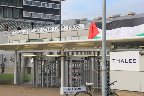 [Photo: Glasgow Palestine Action on top of the roof of Thales in Govan, who manufacture components for drones that are sold to Israel, unfurls a banner 'Another Scotland is Possible. Stop Arming Israel' on 23 September 2014]