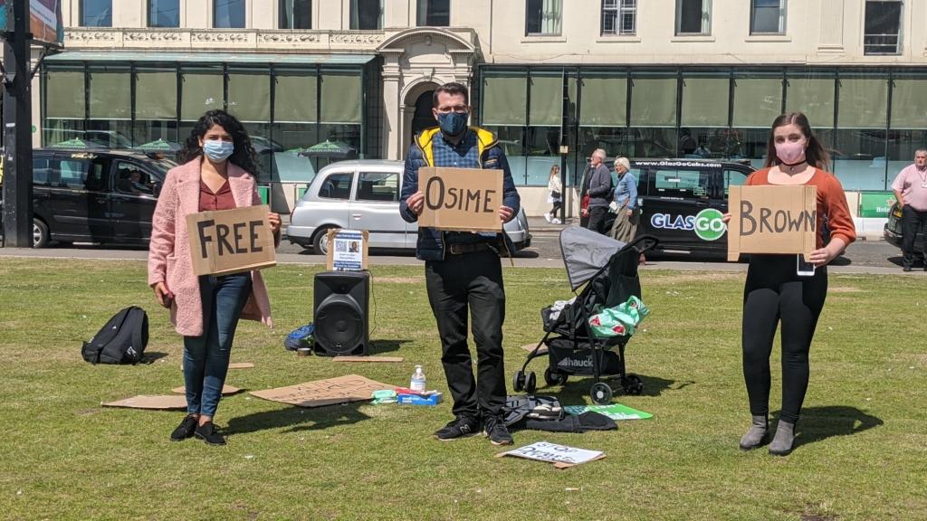 "Roza Salih, Paul Sweeney MSP, and Chloe Whyte holding signs saying ""free osime brown"""